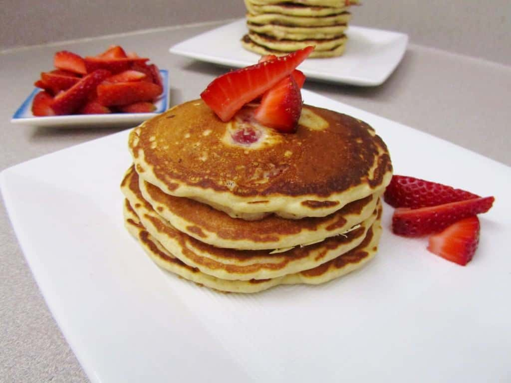 Stack of four pancakes garnished with sliced strawberries on square white plate.