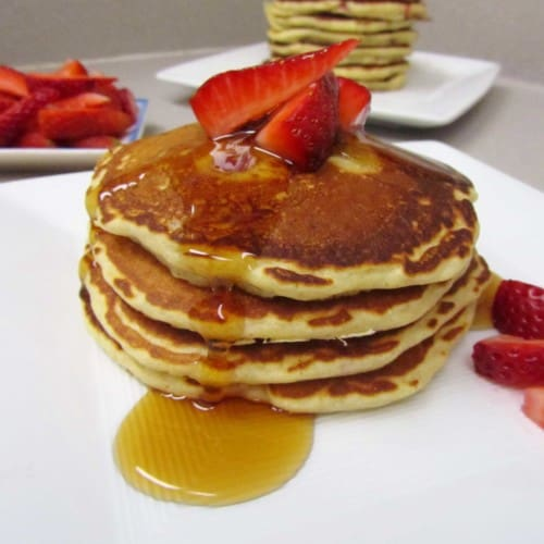 Stack of pancakes with maple syrup and fresh sliced berries, on white plate.