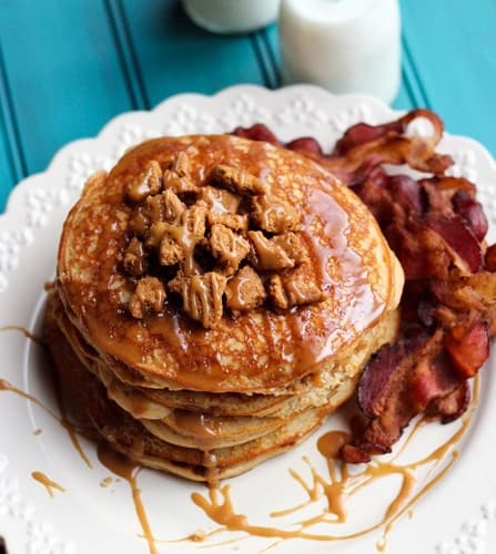 Stack of pancakes on white plate, with syrup and bacon.