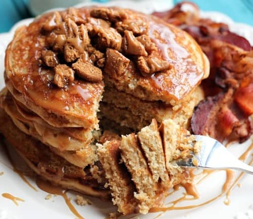 Stack of pancakes with bite removed, accompanied by bacon.