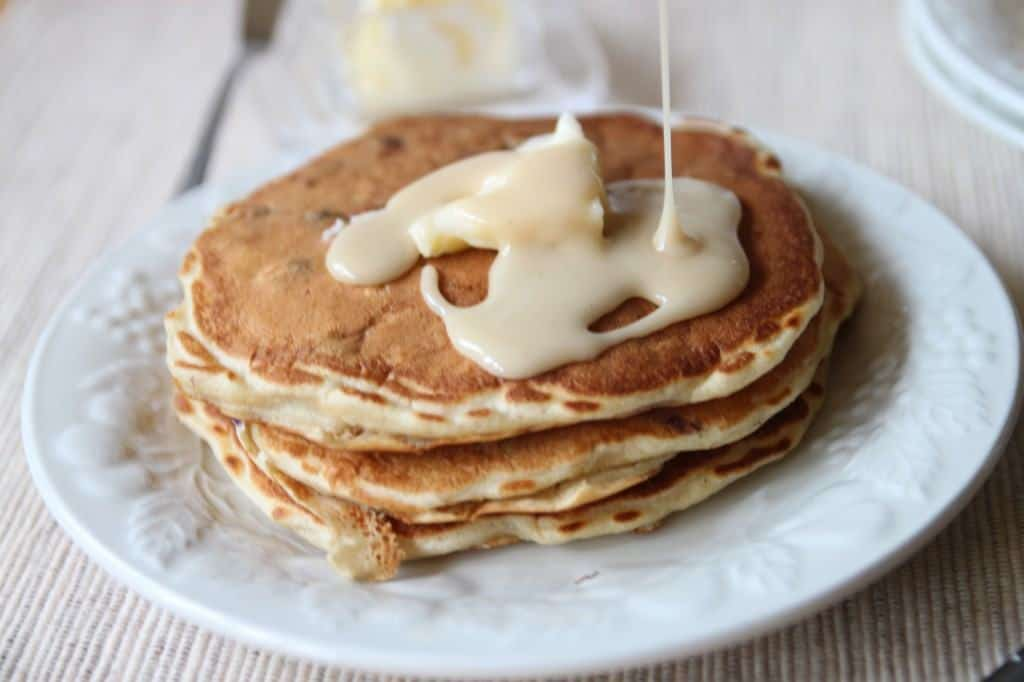 Short stack of pancakes on white plate with glaze being drizzled on.