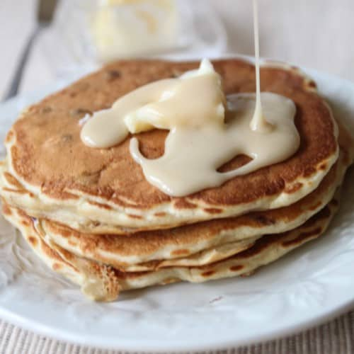 Stack of three pancakes on white plate with butter and maple vanilla syrup.