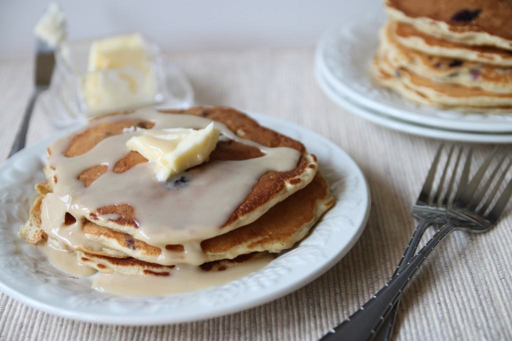 Stack of pancakes on white plate, topped with butter and glaze, with more pancakes in background.