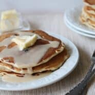Stack of pancakes with butter and glaze on white plate with more pancakes in background.