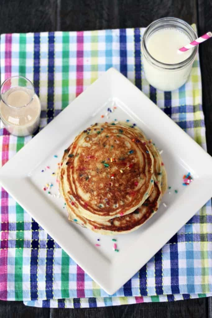 Overhead of pancakes on plate, with glass of milk and clear glass pitcher of glaze.