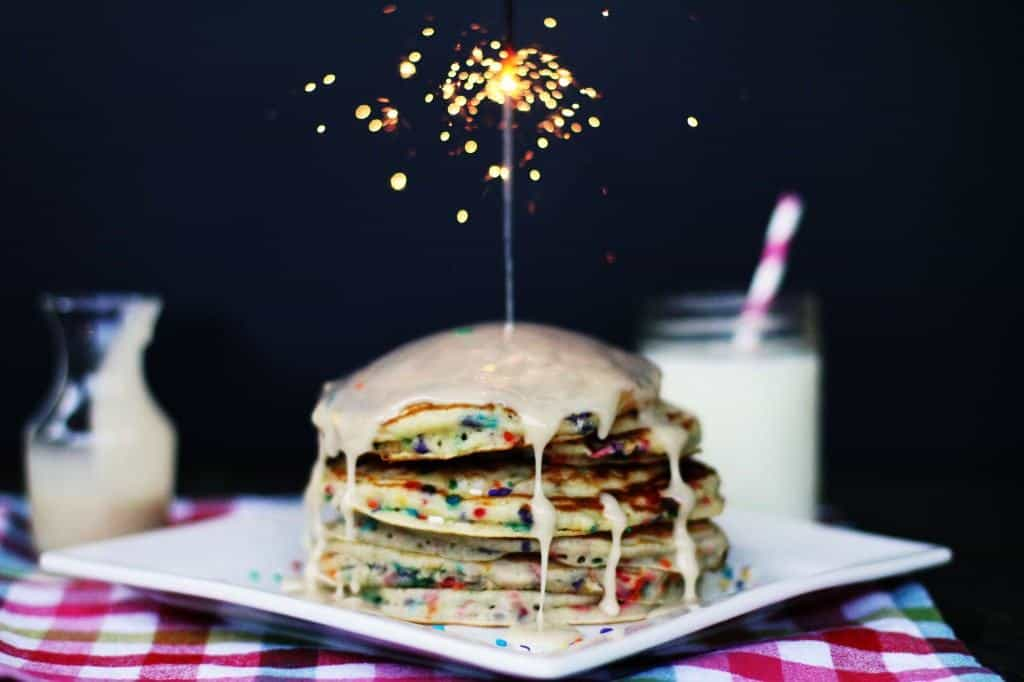 Stack of pancakes topped with glaze and lit sparkler.