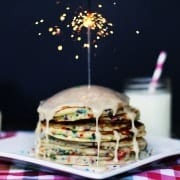 A stack of pancakes topped with lit sparkler.