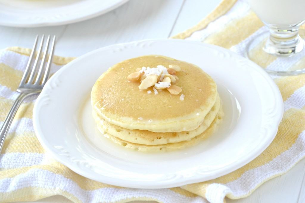 Stack of three pancakes on white plate, garnished with macadamia nuts.
