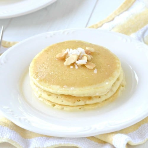 Stack of pancakes on white plate, garnished with chopped nuts.