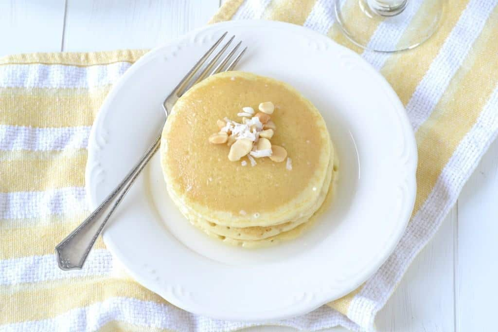 Overhead of pancakes on plate with fork, on yellow striped cloth.