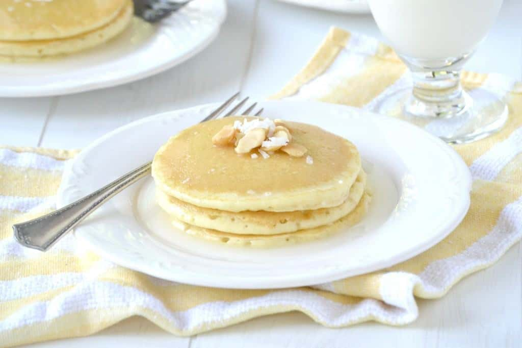 Stack of three pancakes on white plate with fork.