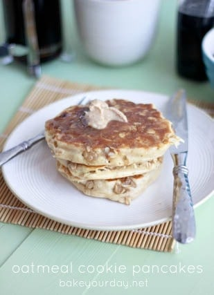 "Front view of a stack of three pancakes, on a white round plate, with knife and fork also on plate. Text overlay reads ""Oatmeal cookie pancakes Bakeyourday.net"""
