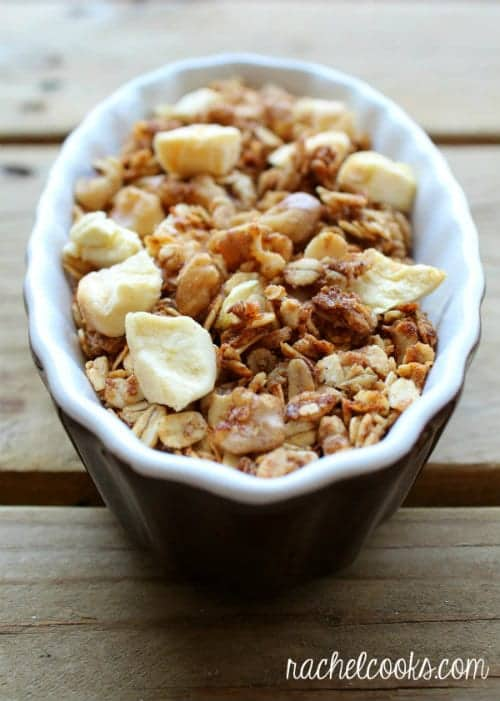 Overhead view of small brown and white ceramic dish with a serving of apple granola.