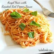 "Front view of square white plate containing a serving of pasta, garnished with fresh basil leaves. Text overlay reads ""Angel hair with roasted red pepper sauce."""