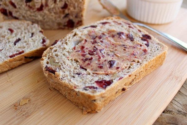 A slice of cranberry walnut bread spread with cranberry butter.