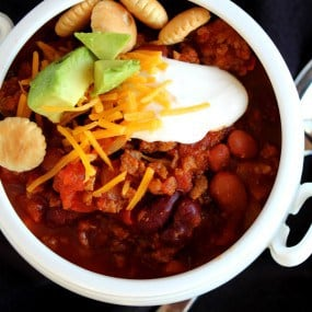 Chili topped with cheese, sour cream, oyster crackers, and avocado.