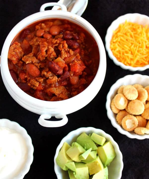 Overhead view of a white bowl of chili surrounded by small bowls of toppings: cheese, crackers, avocado, sour cream.