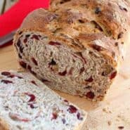 Partially sliced loaf of cranberry walnut bread on cutting board.