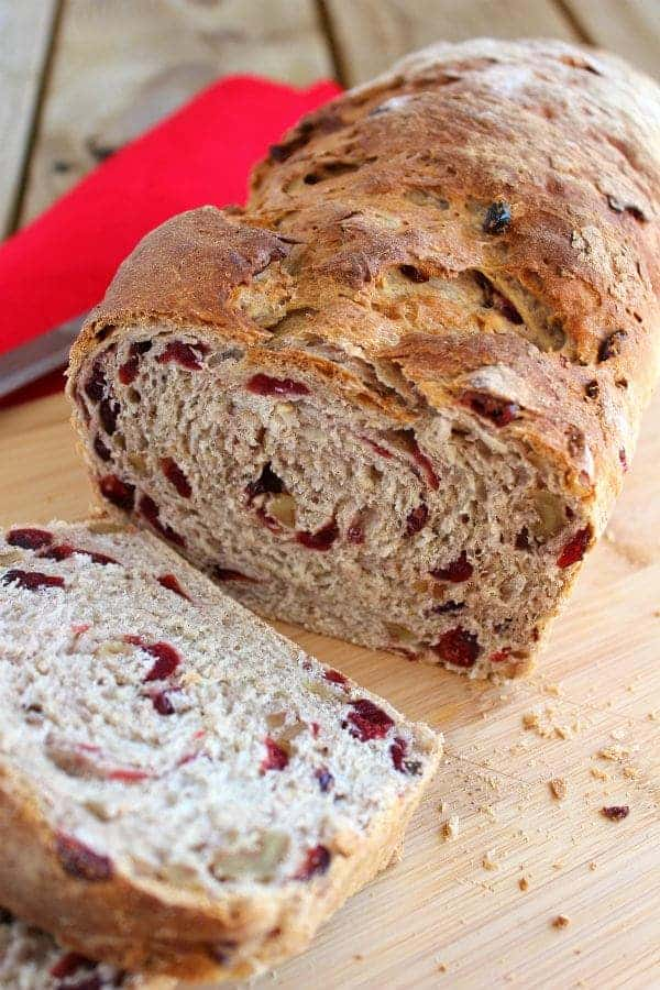 Loaf of cranberry walnut bread, partially sliced on wooden cutting board.