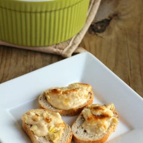 Three crostini with cheddar leek dip arranged on square white plate.