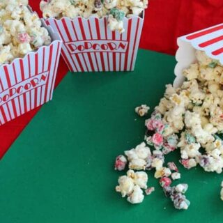 Peppermint popcorn spilling out of a popcorn container onto a green surface.