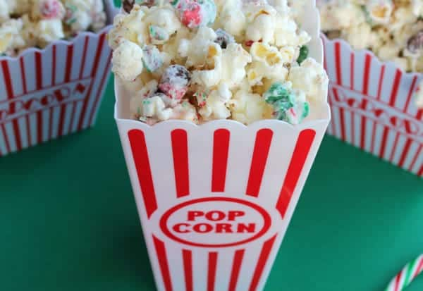 Peppermint and white chocolate coated popcorn in a plastic popcorn container.
