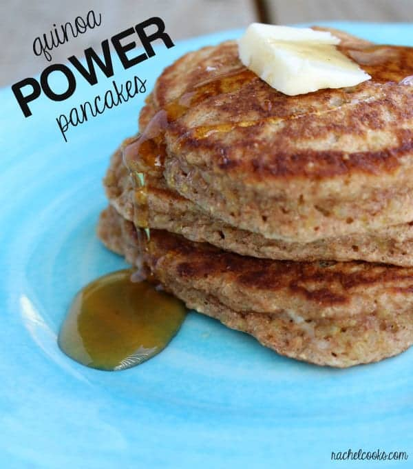 """Partial front view of stacked pancakes on bright blue plate, with butter and syrup. Text overlay reads """"quinoa power pancakes."""""""