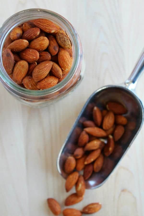 Almonds on a scoop and in a jar on a wooden surface.