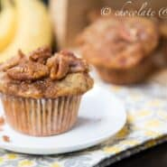 "Front view of one banana streusel muffin on small white plate, with bananas and more muffins in background. Text overlay reads ""chocolate & carrots""."