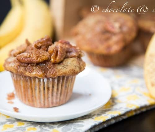 """Front view of one banana streusel muffin on small white plate, with bananas and more muffins in background. Text overlay reads """"chocolate & carrots""""."""