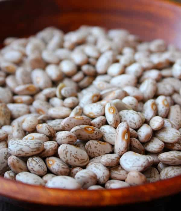 Close up view of uncooked pinto beans in a wooden bowl.