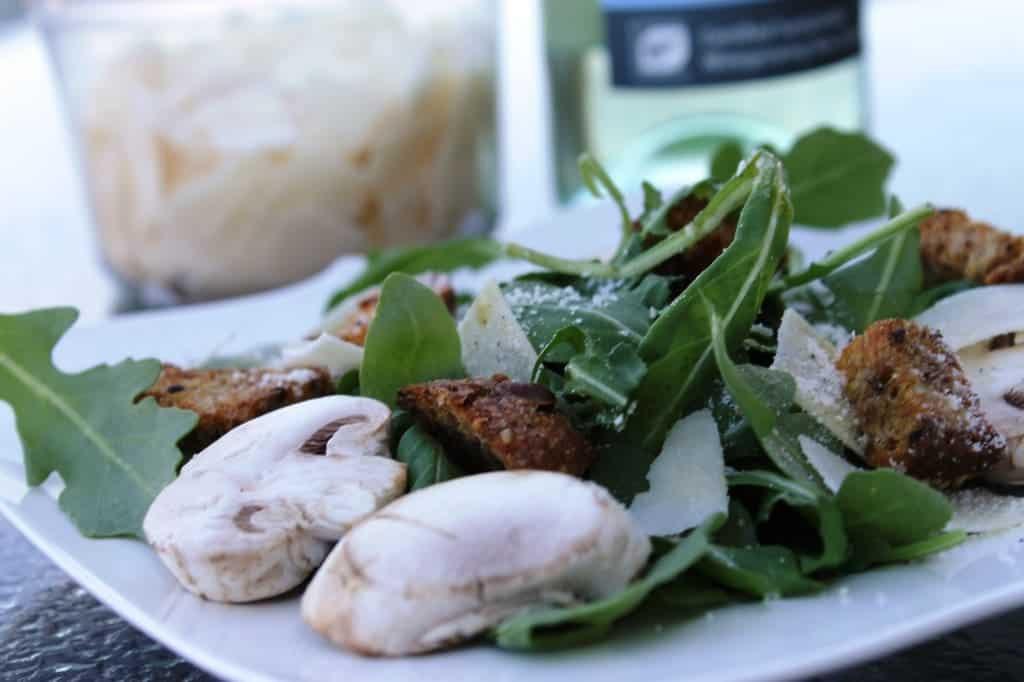 Front view of salad on white plate with Parmesan cheese and white wine bottle in background.