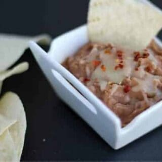 Refried beans in a small white bowl on a black background with a chip being dipped into them.