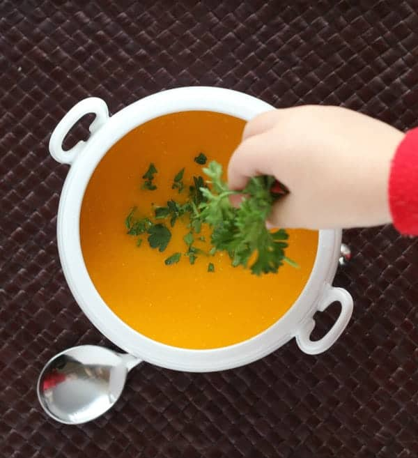 Overhead of bowl of soup with child's hand sprinkling parsley on the soup.