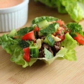 Front view of lamb lettuce wrap with small white bowl of sauce in background.