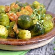 Wooden bowl containing Brussels sprouts with smoked paprika and shallots.