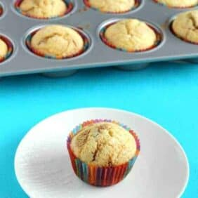 Muffin on a white plate with a bright blue background, more muffins in a tin in the background.