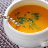 Closeup of squash soup in white bowl with spoon inserted.