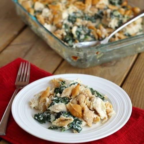 Chicken and kale casserole on white plate, with clear glass casserole pan in background.