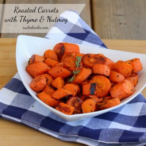 Roasted carrots in white bowl on blue checked folded napkin.