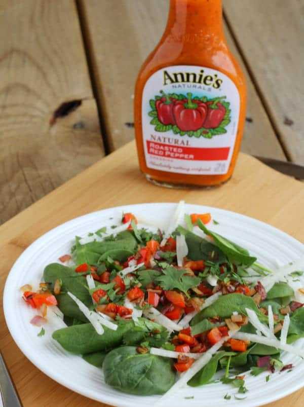 Front view of salad with dressing bottle behind it.