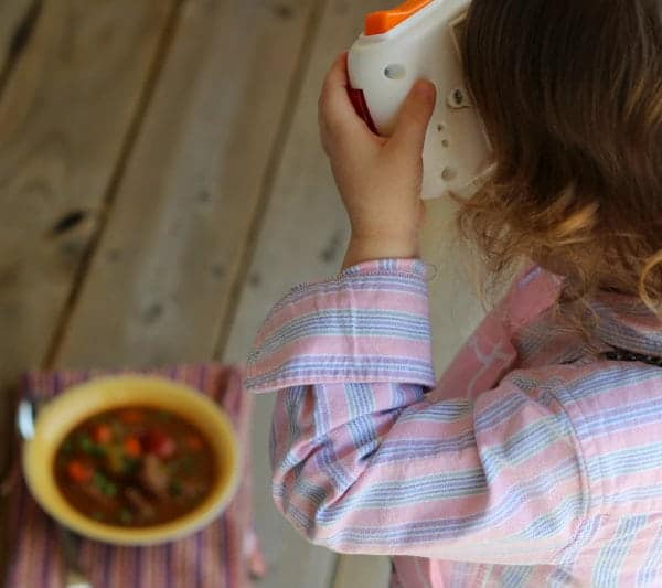 Young girl taking a picture of beef stew with a toy camera.
