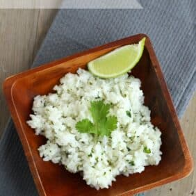 Overhead view of rice in a square wooden bowl, garnished with cilantro leaf and wedge of lime, on a gray cloth. Text overlay reads Cilantro-Lime Rice.