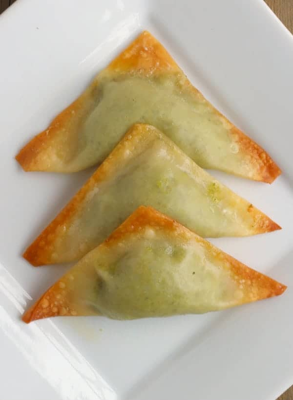 overhead view of 3 baked pea dumplings arranged on square white plate.