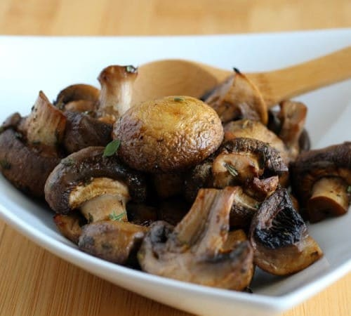 Close up of white dish containing roasted mushrooms and wooden spoon.