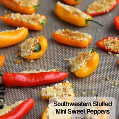 Stuffed mini peppers arranged on baking sheet.