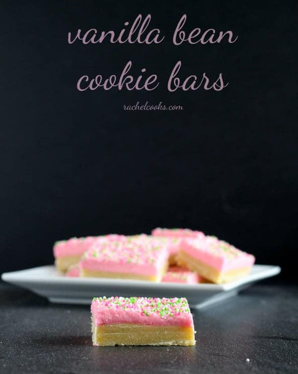"Front view of several cookie bars on white plate, with one bar on surface in front of plate. Text overlay reads ""vanilla bean cookie bars. Rachelcooks.com""."
