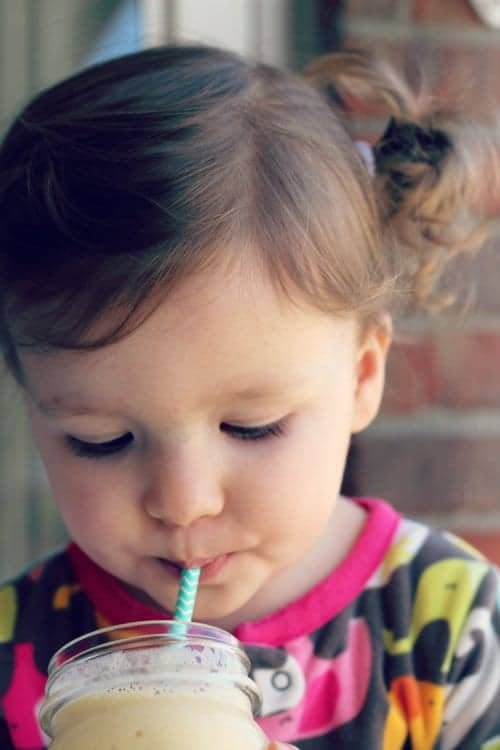 Head shot of toddler girl with pigtails sipping on smoothie through a straw.