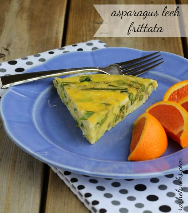 "Front view of slice of asparagus leek frittata on a blue plate, with fork and orange wedges. Text overlay reads ""Asparagus leek frittata."""