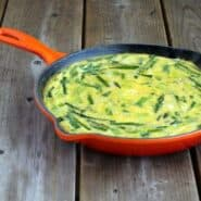 Orange skillet containing asparagus leek frittata on wooden deck background.